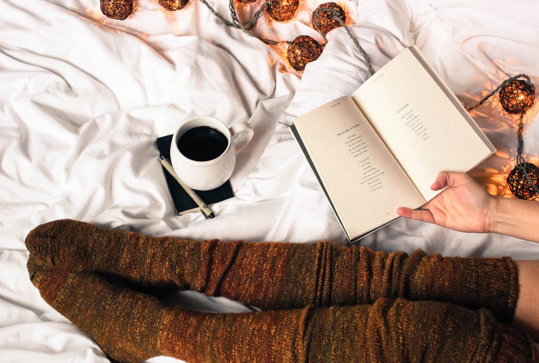 Person leser bok i sengen - les våre boktips til jul her